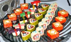 Candy sushi rolls are made with rice crispy treats, wrapped with fruit rollups and topped with a variety of candies to include kosher Swedish fish, rock candy, colorful marshmallows, sour straws, and  licorice to name a few.  Can you pick out some other candy?