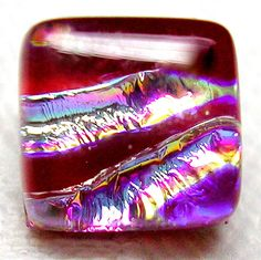 "STELLAR RED DICHROIC ART GLASS BUTTON w/SHIMMERING PASTEL RAINBOW HUES   FUSED DICHROIC ART GLASS STUDIO BUTTON WITH A DEEP RED OPAQUE GLASS BASE AND THE MOST DELIGHTFUL SILVERY RAINBOW HUED GLASS ON THE TOP-IT MEASURES A HAIR UNDER A HAIR OVER 3/8"" SQUARE, IS ABOUT 1/4"" THICK AND IT HAS A SILVER PLATED METAL LOOP AND PLATE SHANK ON BACK-IT IS IN PRISTINE/UNUSED CONDITION  SOLD $39.00"
