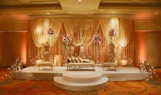 Gold color Muslim Wedding ceremony Stage decor contains golden backdrop drapery with flowers, 2 elegant golden tan chairs, a golden bench with cushions and containers of water with candles.