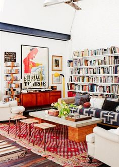 Eclectic living room with lots of bookshelves, a mid-century sliding door credenza, Nordic textiles and a bold red and white Moroccan area rug.