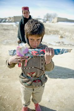 """""""Afghan Boy With Wooden Rifle"""". Future friend or foe? Location: Paktika Province, Afghanistan. (Photo and caption by Alex Manne/National Geographic Traveler Photo Contest)"""