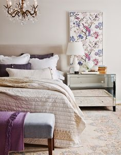 Sophisticated Bedroom - Layered with a quilted coverlet, neutral bedding and cable-knit throw pillows. Opulence introduced by the mirrored furniture and chandelier keeps it from feeling too casual. Using a three-drawer dresser in place of traditional bedside tables reduces the number of pieces needed and opens up the room.