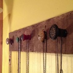 Took a piece of old barn wood, bought cool knobs from hobby lobby (50% off so they cost around $1.50 a piece) drilled holes in the board and attached the knobs. It was around a $5 project and my necklaces have a pretty place to hang!! :)