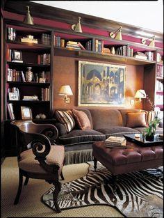 Deep Plum wall, fringe sofa, zebra rug and leather ottoman