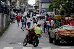 People run away from police (on motorcycle) during riots for food in Caracas, Venezuela, June 2, 2016. REUTERS/Marco Bello