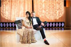 Indian bride wearing beige lengha and groom wearing a black suit and bow tie ~ Photo: Biyani Photography