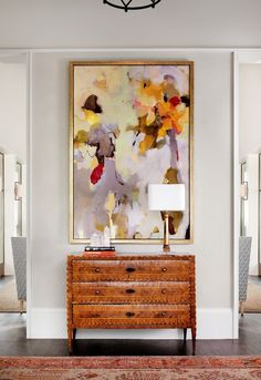"a favorite art display via FHD: ""One large, powerful, impactful piece is made the focus of the room// The pop of gorgeous colors – I'm loving the lavender and tangerine combo//  In LOVE with the gold, crisp frame//  The modern art set against the antique burl wood piece// How the art and the dresser fill the height of the room."""