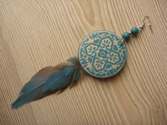 Blue earring with inlay on wood. This earring has the size of about 14 cm and is decorated with two blue feathers of the Amazon parrot.