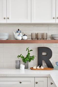 White shaker cabinets accented with nickel knobs are mounted to white stacked backsplash tiles above a long stained wood shelf and a black wood letter. Shelves Over Kitchen Sink, White Kitchen Cupboards, White Shaker Kitchen, Kitchen Wall Cabinets, White Shaker Cabinets, Kitchen Cabinet Design, Kitchen Redo, Home Decor Kitchen, Kitchen Interior