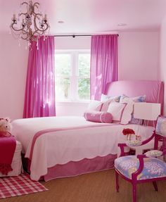 Pink girl's bedroom features twin bed place din corner of room dressed in hot pink slipcovered headboard with matching bedskirt as well as white and pink scalloped bedding and pink monogrammed bolster pillow as well as white ottoman at foot of bed atop pink gingham rug situated next to windows dressed in hot pink curtains.