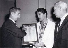 """Elvis receiving his """"No. 1 in the Nation"""" award for """"Roustabout"""" album on the movie set of """"Harum Scarum."""" Handing out the award is Grelun Landon, (left) RCA West Coast press and information director and W. T. Baker (right) RCA field sales representative."""