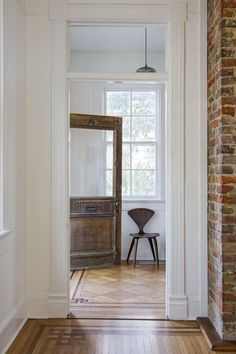 """farmhousetouches: """" Remodelista In the entryway, the original, carved wood door mixes with a chair by Bauhaus-educated designer Norman Cherner and a commissioned pendant light by third-generation woodworker Emily Brock of Board & Bread. Interior And Exterior, Interior Design, Interior Architecture, Charleston Homes, European Home Decor, Deco Design, Eclectic Decor, Contemporary Decor, Modern Decor"""