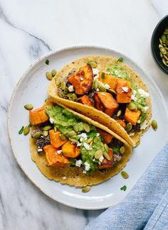 These roasted sweet potato tacos feature spicy black beans and avocado-pepita dip