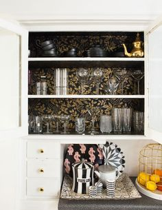 Black and gold wallpaper covers the inside of white kitchen cabinets.