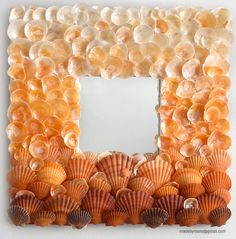 shell-framed mirror - photo only - diy suggestion: cut a square from wood/plywood; paint white or light color; hot glue small mirror to center; hot glue shells in attractive pattern (here, an ombre effect)