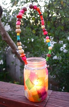 Make a lantern with your kids using a jar, tissue paper, and beads!