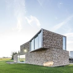 the narrow, long, and tall house sits upon a beautiful site with endless views of the green landscape in bierbeek, belgium.