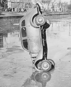 A number of the shots in the Jones collection involve cars being hauled out of water and here a car lies completely upright before it is taken out of a canal