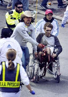 The man in the cowboy hat, Carlos Arredondo, was at the Boston Marathon with his wife handing out American flags when the bombs exploded. He immediately ran towards the danger, jumped two fences and found the now-famous man in the wheelchair on the ground, both his legs blown off, and suffering from severe shock and critical wounds. He got him into a wheelchair and pinched the man's artery closed with two of his fingers. Because of Carlos, this man is alive today.