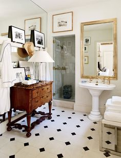 black and white prints and an antique console in the bathroom