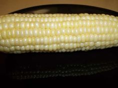 Get out your corn on the cob (husk and all) and place it in your microwave. Cook the corn on full power for 5 minutes. Remove the corn from the microwave using oven mitts and cut about 1 inch off the bottom. Hold the corn up from the opposite side and it will easily slide down and out... completely clean.