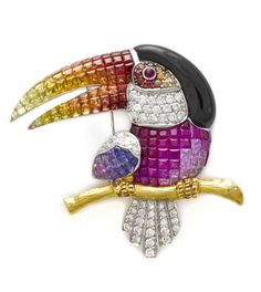 A multi-color sapphire, garnet, black onyx and diamond toucan brooch composed of calibré-cut multi-color gems and round brilliant-cut diamonds; mounted in eighteen karat bicolor gold; length: 1 3/4in. (one purple sapphire deficient)