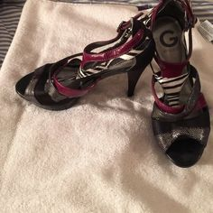 Guess Heels Like new! Worn once but you can still see the tag wasn't even worn off. No scuffs. Metallic black with a maroon/purple and zebra straps. Guess Shoes Heels