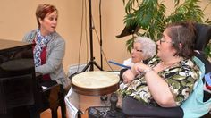 Music therapist Lara Robinson shares a song with Cedarstone Enhanced Care residents Mildred Porter and Tonya Dean in Truro. Robinson manages the newly launched iPod Pharmacy in the area, taking donated iPods and loading them with music to meet clients' needs and musical preferences.