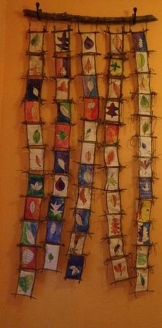 Watercolor leaf paintings on book pages, hung using branches, sticks, and yarn. by tonya