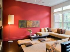 Modern living room with red walls, furnished with a brown sofas cream