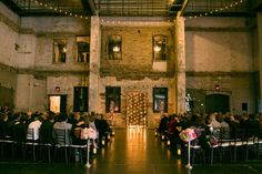 Industrial+Ceremony+Site+with+Gleaming+Lights+and+Pink+Flowers+|+Erin+Johnson+Photography+|+See+More!+http://heyweddinglady.com/romantic-industrial-glam-wedding-from-erin-johnson-photography/