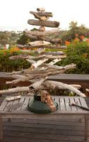 This may be more of a nautical theme, but I picked up driftwood on my last trip to the gulf so I could make one of these trees for my garden. I bought two starfish for the top!