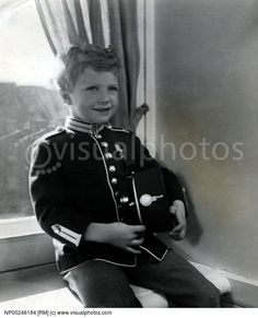 Portrait of a young Carl XVI Gustaf sitting on windowsill while holding cap