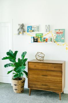 White nursery // fiddle leaf fig tree // retro chest of drawers // wall shelves for books etc.