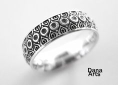 I wear this ring with the pattern on the inside.  I love it.    His and her matching bands by DanaArts  $250