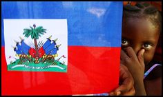 Malik Desange of Arcahaie, Haiti peers from behind a Hatian flag on May 18, 2010. Arcahaie is the birthplace of the Haitian flag.
