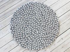 Ein schöner und langlebiger klassischer Teppich aus Wollfilzkugeln. Der Kugelteppich setzt sich aus weißen, hellgrauen und naturgrauen Wollfilzkugeln zusammen. Die Farben sind besonders in Kombination mit Leder- und klassischen Möbeln beliebt. Im Gegensatz zum Multi Color, hat dieser Teppich eine ruhigere Ausstrahlung und ist weniger dominant.