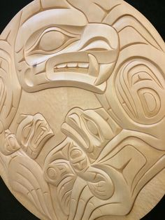 This Bear Mother panel was carved from yellow cedar by Coast Salish artist Aubrey LaFortune. The Bear Mother is depicted at the top with her two cubs in her embrace. Good Cub wants to be just like Mom, and has his teeth bared like her, while Cheeky Cub hides his teeth defiantly. Measures 24 inches across and 1