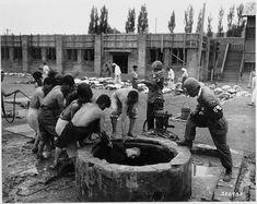 1950년 10월 19일 북한군 포로들이 국군 헌병의 감시 아래 함흥의 우물 속에 버려져 있던 민간인 시체 65구를 끌어내고 있다.