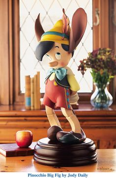 "PINOCCHIO BIG FIG Designed by Jody Daily Resin, Wood Base, and Fabric Bow. Released in 2005. © Disney We've always loved Pinocchio with his ""jack ass"" ears and tail!"