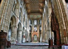 Catedral de Peterborough. Fundada en el periodo sajón, pertenece fundamentalmente a la arquitectura normanda, tras su remodelación en el siglo XII. es conocida sobre todo por su fachada oeste, de estilo gótico perpendicular, con sus tres enormes arcos, a la cual no se le conocen precedentes ni sucesores directos. La apariencia del edificio es ligeramente asimétrica, dado que una de las torres nunca fue terminada de edificar.