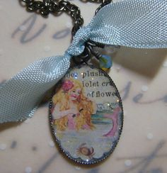 A collage made with a vintage illustrations and German glass glitter and set into a gunmetal plated bezel pendant and covered with a protective layer of resin. A swarovksi and a czech glass glass crystal each dangle with a little ribbon from an 18 inch gunmetal plated chain with lobster clasp. Ive added a photo of a similar pendant to give an idea of what the pendant will look like on. All jewelry will be packaged in a way to make it perfect for gift giving