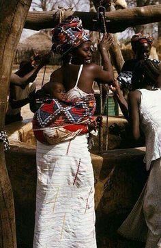 Algumas mães senegalesas carregam seus filhos junto às suas costas, geralmente com tecidos bem coloridos. Some of the Moms in Senegal carry their babies tied onto their backs, usually with colourful material.