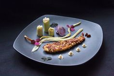 Fried flatfish coated with nuts - served with root vegetable chips and small leek towers