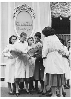 """The """"Catherinettes"""" of the Maison Christian Dior atelier reads in the newspaper announcing the sudden death of the designer, photographed by Jose Burreta, 1957"""