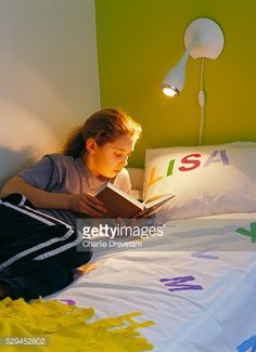 Stock Photo : Girl lying in bed reading