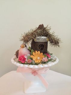 """This darling little bird is ready to bring in the spring complete with his nest of flowers, """"Gratitude"""" birdhouse, tinsel and glitter. He's nestled in a vintage milk glass compote embellished with a pink velvet bow and millinery flowers.     This handmade and one-of-a-kind creation measures approximately 5 """" tall and 4"""" wide.   Shop this product here: spreesy.com/oliveandtrixie/16   Shop all of our products at http://spreesy.com/oliveandtrixie      Pinterest selling powered by Spreesy.com"""