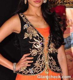 #Desi #FW13: Nargis Fakhri wears an embroidered waist coat in black with gold zari work over orange Anarkali with golden borders (2012)