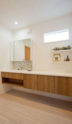 既製品と造作を組み合わせた洗面化粧台。洗濯室と脱衣室を兼ねているので、広いカウンターは奥様にはうれしいスペース。