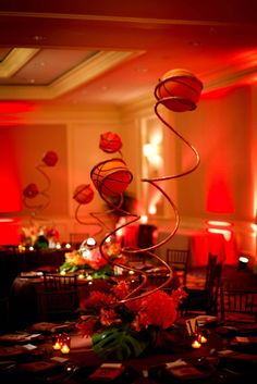 centerpieces with wires and basketballs with flowers and foliage at the base | brad austin